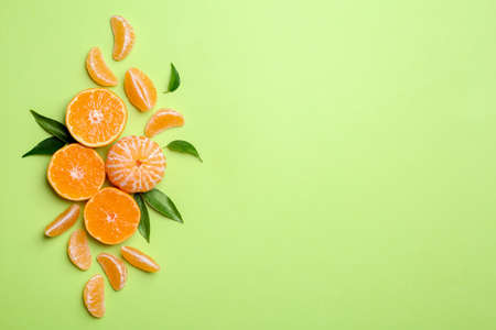 Composition with tangerines and leaves on color background, flat lay. Space for text