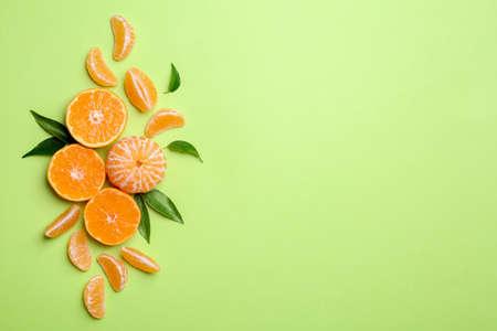 Composizione con mandarini e foglie su sfondo colorato, distesi piatti. Spazio per il testo
