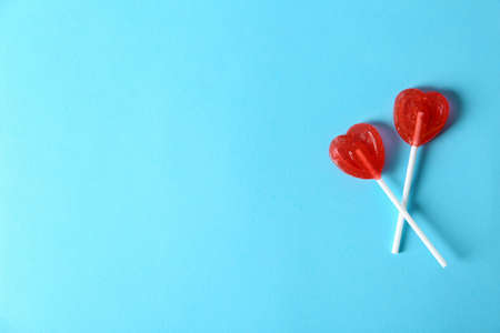 Heart shaped lollipops and space  text  color background, top view. Sweet love