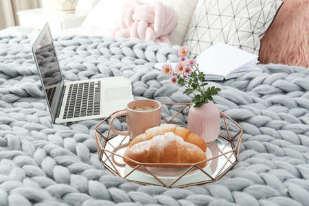 Tray with tasty breakfast, laptop and book on bed