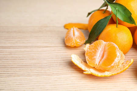 Fresh ripe tangerines with green leaves on table. Space for text