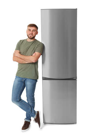 Young man near closed refrigerator on white background
