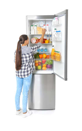 Young woman taking cheese from refrigerator on white background Фото со стока