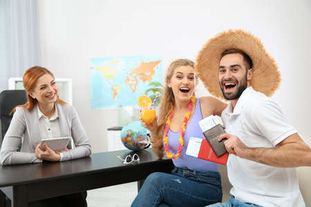Beautiful young couple visiting travel agency office Stock Photo