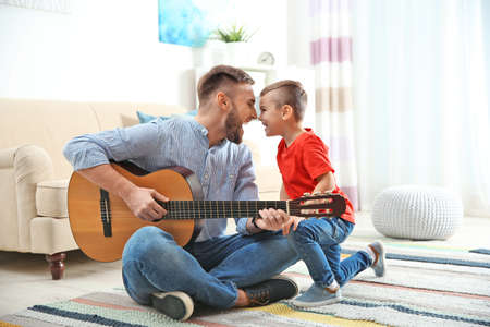 Father playing guitar for his son at home