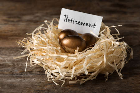 Golden eggs and card with word RETIREMENT in nest on wooden background. Pension concept
