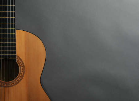 Beautiful classical guitar on gray background, top view with space for text. Musical instrument
