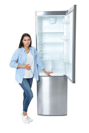 Hungry woman near empty refrigerator on white background