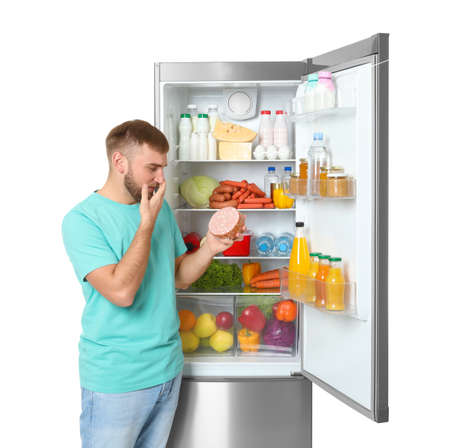 Young man with expired sausage near open refrigerator on white background