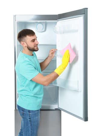 Young man cleaning refrigerator with rag on white background
