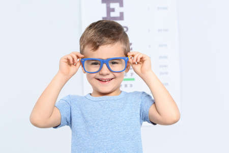 Little boy with glasses visiting children's doctor in clinic, space for text. Eye examination