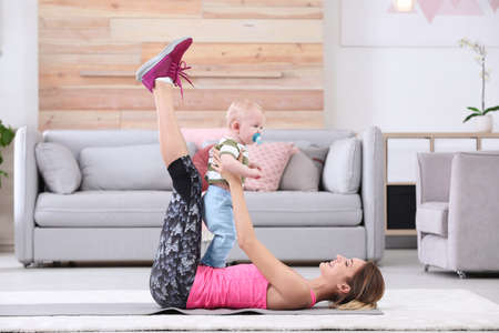 Young sportive woman doing exercise with her son at home. Fitness training 写真素材