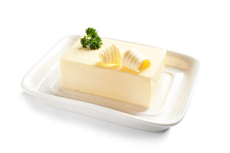 Ceramic dish with block of fresh butter on white background