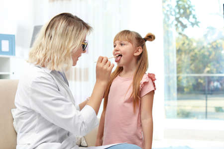 Children's doctor examining little girl's throat at home. Space for text