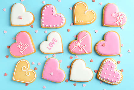 Composition with decorated heart shaped cookies on color background, top view. Valentines day treat