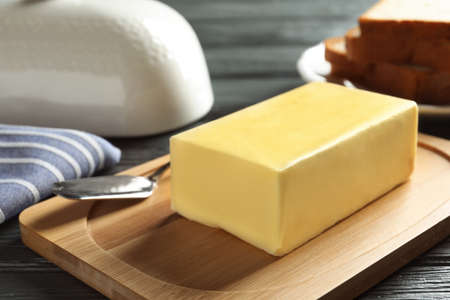 Wooden board with fresh butter and knife on table, closeup