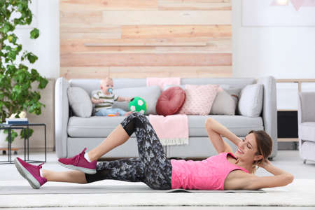 Young sportive woman doing exercise while her son sitting on sofa at home. Fitness training