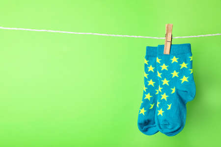 Cute child socks on laundry line against color background. Space for text Imagens