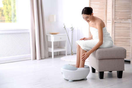 Woman with beautiful legs using foot bath at home, space for text. Spa treatment Banque d'images