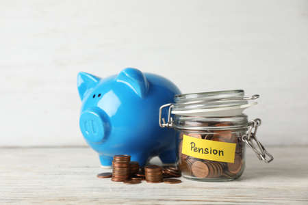 Piggy bank and jar of coins with word PENSION on table