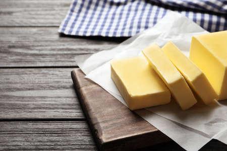 Tabla de madera con mantequilla fresca en la mesa. Espacio para texto