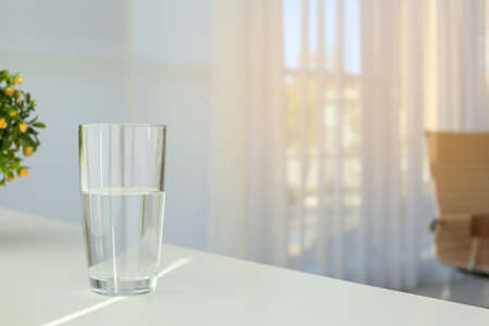 Glass of water on table indoors. Space for text