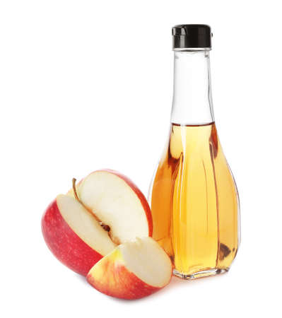 Glass bottle of vinegar and fresh apple on white background