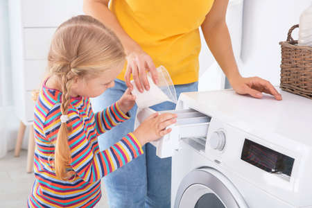 Little girl helping her mother to do laundry at home 免版税图像 - 113645406