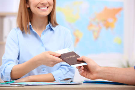 Female manager giving passport with ticket to client in travel agency