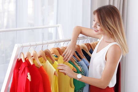 Beautiful young stylist choosing trendy clothes from rack in studio Stock Photo - 113446047