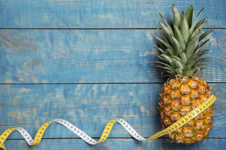 Flat lay composition with pineapple, measuring tape and space for text on wooden background. Weight loss concept Foto de archivo - 113446073