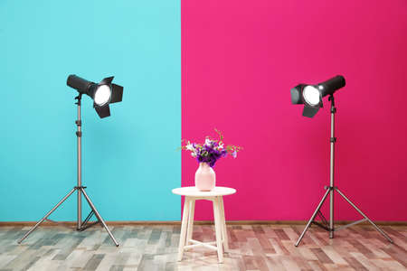 Professional lighting equipment and vase with flowers on table near wall in photo studio Banco de Imagens