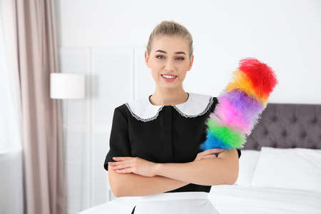 Young chambermaid with dust brush in bedroom