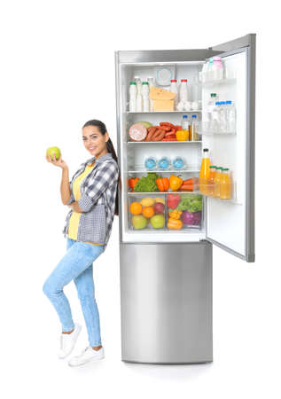 Young woman with apple near open refrigerator on white