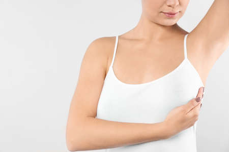 Woman checking her breast on white background, closeup