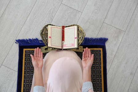 Muslim woman reading Koran indoors, top view