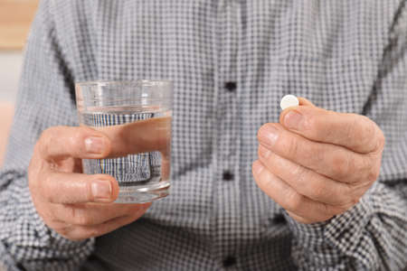 Senior man holding pill and glass of water, closeup