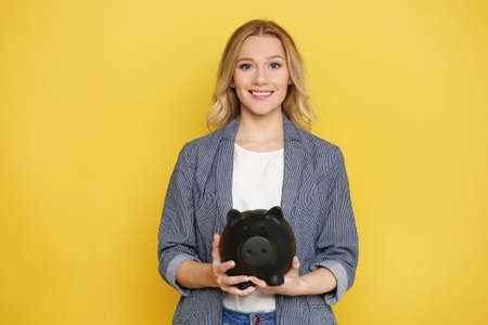 Happy young woman with piggy bank on color background