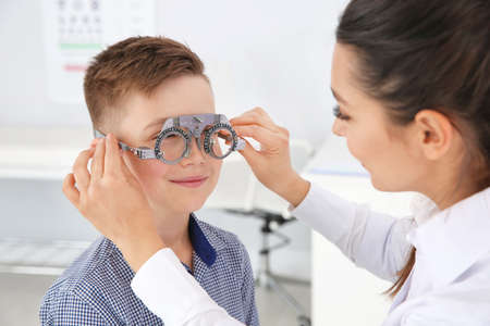Childrens doctor putting trial frame on little boy in clinic. Eye examination