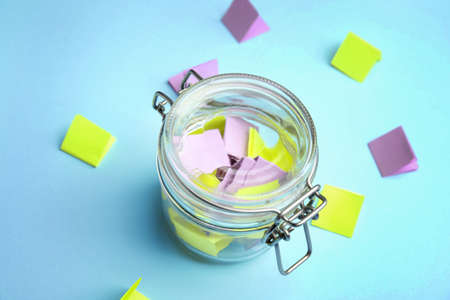 Glass jar and paper pieces for lottery on color background 版權商用圖片