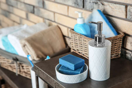 Dish with soap bars and bottle of shampoo on table near brick wall