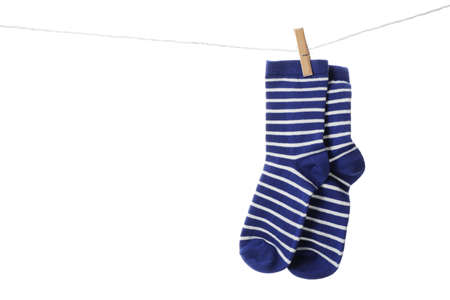 Cute child socks on laundry line against white background
