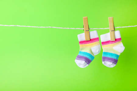 Cute child socks on laundry line against color background. Space for text Stock Photo