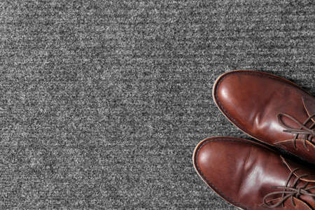 Brown classic shoes on gray doormat, top view. Space for text