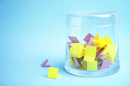 Glass container and paper pieces for lottery on color background. Space for text