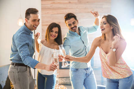 Friends clinking glasses with champagne at party indoors Banco de Imagens