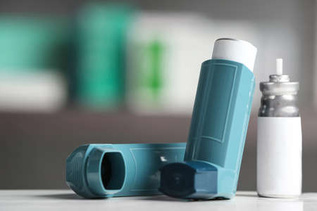 Asthma inhalers on table against blurred background. Space for text