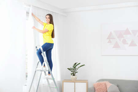 Young woman hanging window curtain in room. Space for text