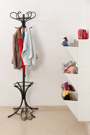 Shoe cabinet with footwear in room. Storage ideas Stock Photo