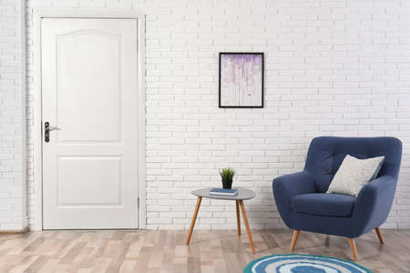 Light room interior with white door in brick wall